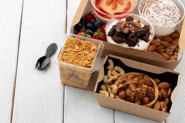 Assortiment van desserts in vakken op witte houten achtergrond