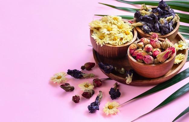Assortiment van droge kruiden gezonde tropische thee in houten kommen op roze achtergrond.