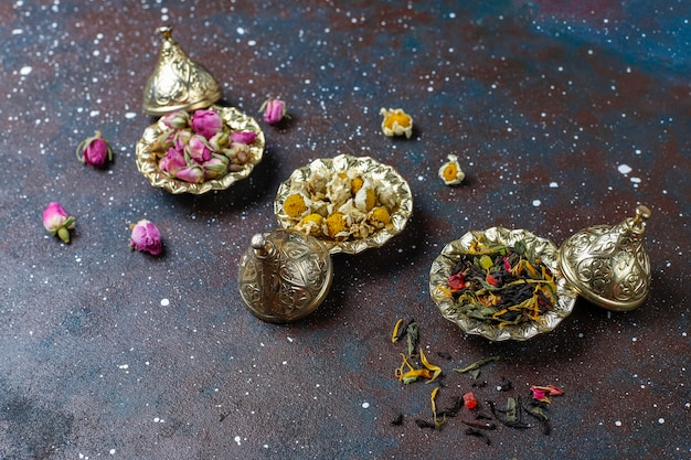 Assortiment van droge thee in gouden vintage mini bordjes. thee soorten achtergrond