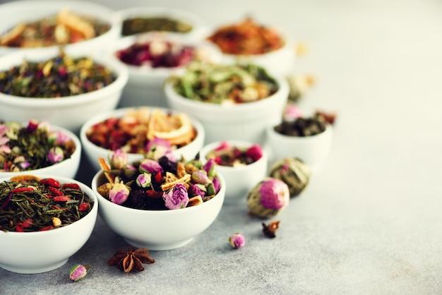 Assortiment van droge thee in kommen. thee soorten: groen, bloemen, kruiden, munt, melissa, gember, appel, roos, lindeboom, fruit, sinaasappel, hibiscus, framboos, korenbloem, cranberry