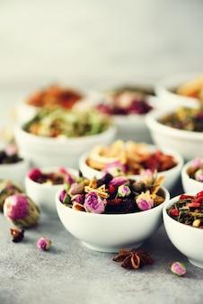 Assortiment van droge thee in witte kommen.