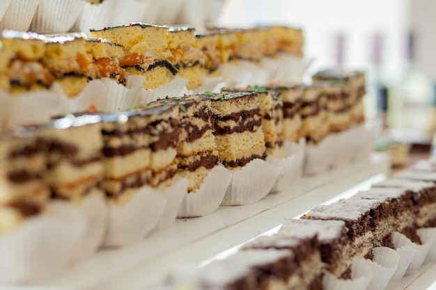 Assortiment van fluitjes van een cent op rommelige tafel, copyspace. verschillende plakjes heerlijke desserts, restaurantmenu, bovenaanzicht