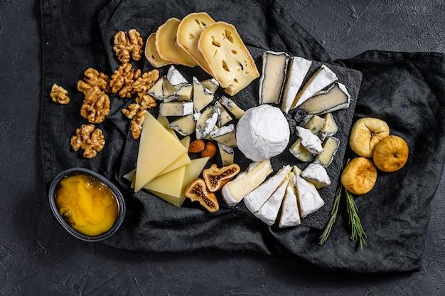 Assortiment van franse kaas met honing, noten en vijgen op snijplank. italiaanse antipasto. zwarte achtergrond. bovenaanzicht