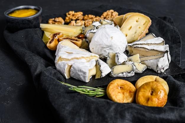 Assortiment van franse kaas met honing, noten en vijgen op snijplank. zwarte achtergrond. bovenaanzicht