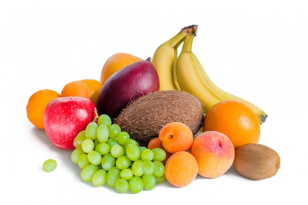 Assortiment van fruitbananen, mango, groene druiven, appel, kokos, perziken, abrikozen, mandarijnen en kiwi is geïsoleerd.
