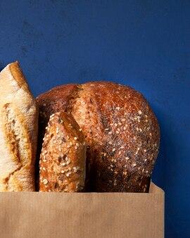 Assortiment van gebakken brood, knapperig stokbrood, bruine en witte tarwekorrelbroden, zaden in het maken van het pakket.