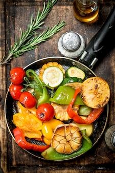 Assortiment van gegrilde groenten met een pan met kruiden en specerijen op een snijplank op houten tafel.