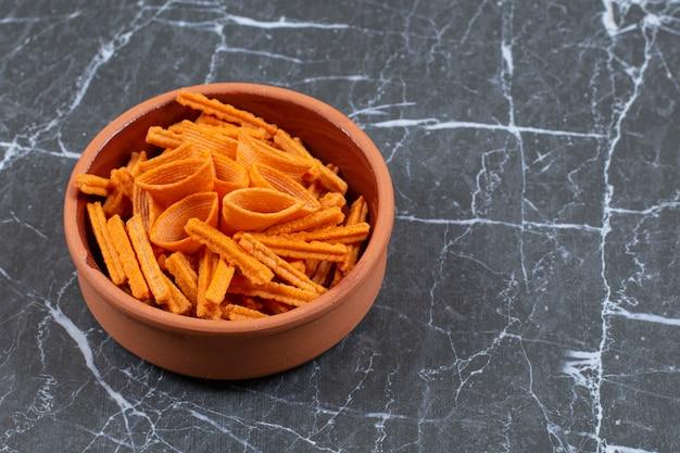 Assortiment van gekruide chips in keramische kom.
