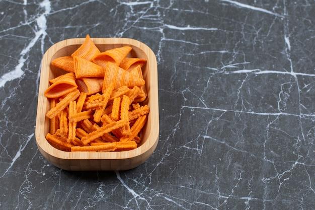 Assortiment van gekruide chips op houten plaat.