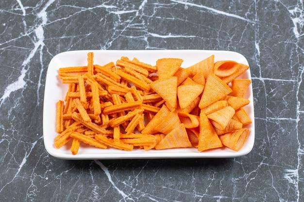 Assortiment van gekruide chips op witte plaat.