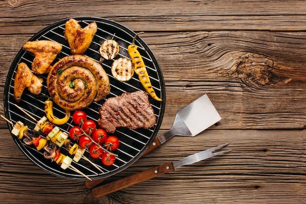 Assortiment van gemarineerd vlees en worsten die bij de barbecuegrill over houten achtergrond roosteren