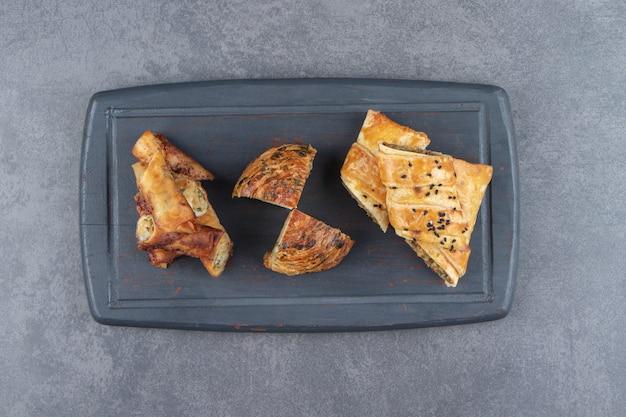 Assortiment van gevulde gebakjes op donker bord.