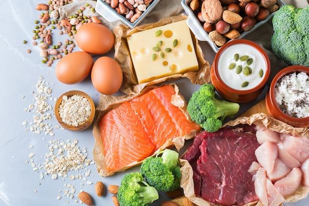 Assortiment van gezonde proteïnebronnen en bodybuildingsvoeding. vlees rundvlees zalm kipfilet eieren zuivelproducten kaas yoghurt bonen artisjokken broccoli noten havermeel. bovenaanzicht