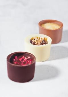 Assortiment van het suikergoedverscheidenheid van de luxe witte en donkere chocolade op witte achtergrond met harde schaduwen