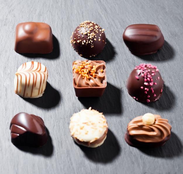 Assortiment van het suikergoedverscheidenheid van de luxe witte en donkere chocolade op zwarte steenachtergrond met harde schaduwen