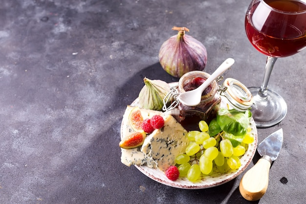 Assortiment van kaas, bessen en druiven met rode wijn in glazen op stenen oppervlak