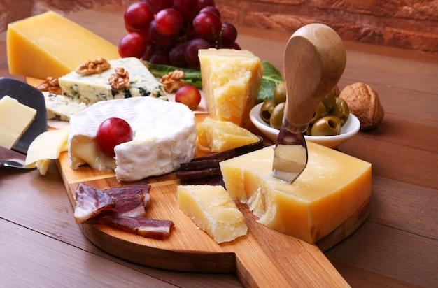 Assortiment van kaas met fruit, druiven, noten en kaasmes op een houten dienblad.