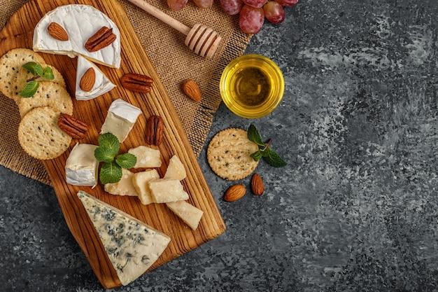 Assortiment van kaas met honing, noten en druiven op een snijplank.