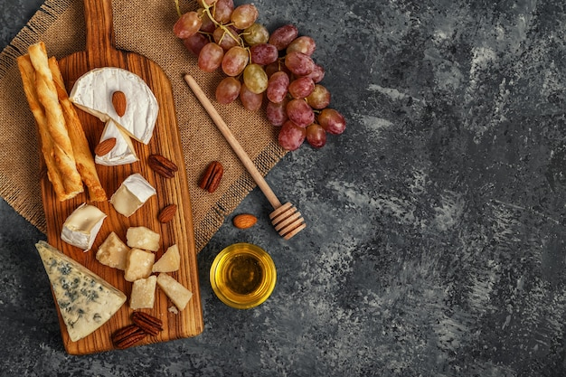 Assortiment van kaas met honing, noten en druivenmost op een snijplank, bovenaanzicht.