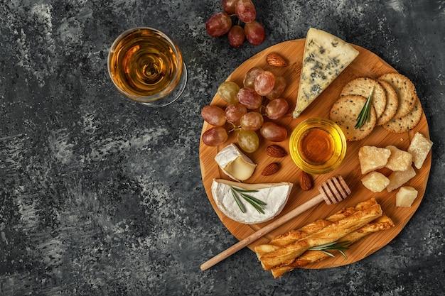 Assortiment van kaas met wijn, honing, noten en druivenmost op een snijplank, bovenaanzicht.