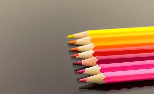 Assortiment van kleurpotloden in een stapel op zwarte achtergrond