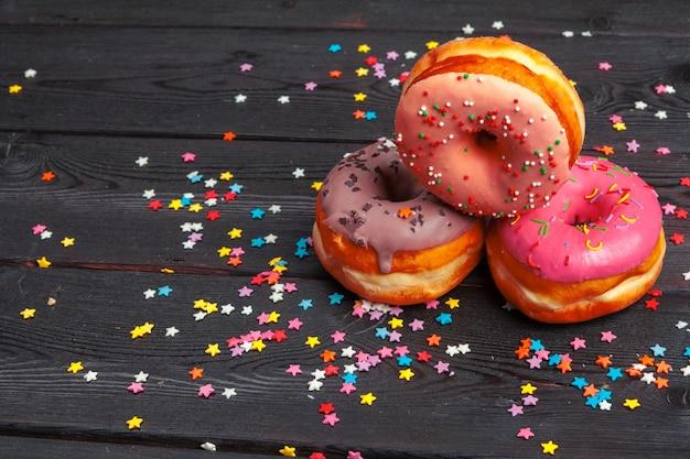 Assortiment van kleurrijke donuts versierd met kleurrijke confetti hagelslag op donkere houten oppervlak