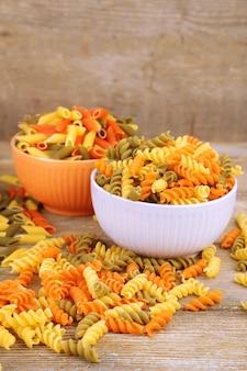 Assortiment van kleurrijke pasta in kleur kommen op houten achtergrond