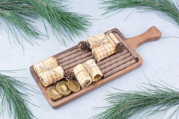 Assortiment van koekjes en gedroogde kiwi op een houten bord.
