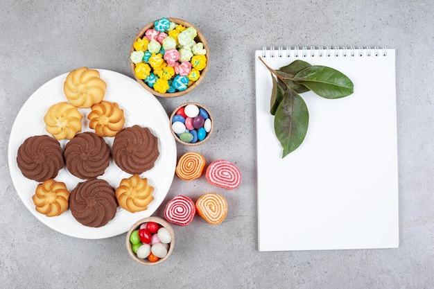 Assortiment van koekjes, snoepjes en marmelade naast wit bord en bladeren op marmeren achtergrond. hoge kwaliteit foto