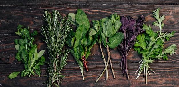 Assortiment van kruiden rozemarijn, rucola, munt, snijbiet, basilicum bovenaanzicht op een houten tafel