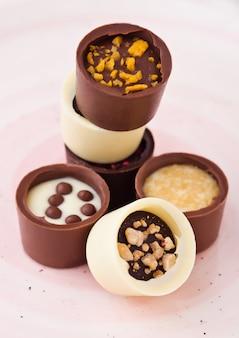Assortiment van luxe witte en donkere chocolade snoepjes variëteit op roze plaat