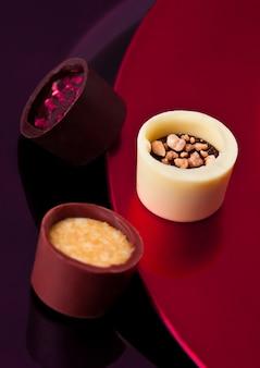 Assortiment van luxe witte en donkere chocoladesuikergoedverscheidenheid op rode en violette plaat