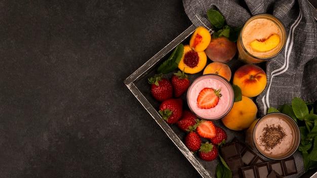 Assortiment van milkshakeglazen op dienblad met fruit en chocolade