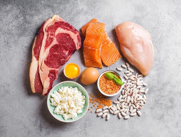 Assortiment van natuurlijke eiwitbronnen uit voedsel: vlees, vis, kip, zuivelproducten, eieren, bonen. dieet, gezond eten, wellness, bodybuilding concept, bovenaanzicht, stenen achtergrond