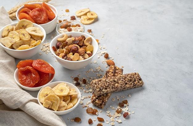 Assortiment van noten, gedroogde vruchten en mueslireep op een grijze muur. zijaanzicht, horizontaal. gezond eten.