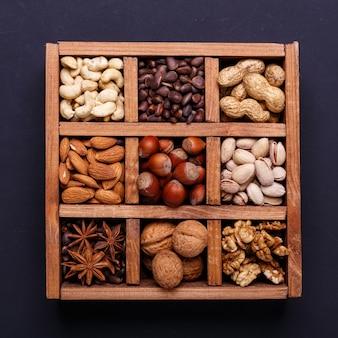Assortiment van noten in een houten doos op een zwarte lei - gezonde snack.