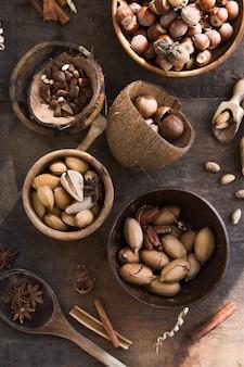Assortiment van noten in een houten kom, op een houten tafel. pecannoten, hazelnoten, amandelen, pijnboompitten, paranoten, cashewnoten, bovenaanzicht, plat.