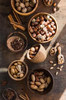 Assortiment van noten in een houten kom, op een houten tafel. pecannoten, hazelnoten, amandelen, pijnboompitten, paranoten, cashewnoten in de schaal. bovenaanzicht, plat lag.