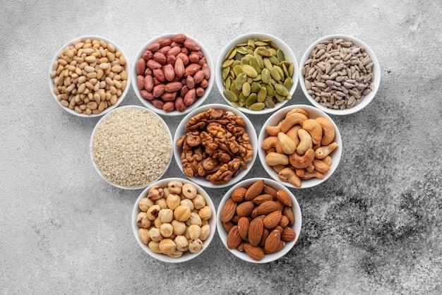 Assortiment van noten in witte schotels op een concrete achtergrond. de mengelingsachtergrond van het voedsel, hoogste mening, exemplaarruimte, banner