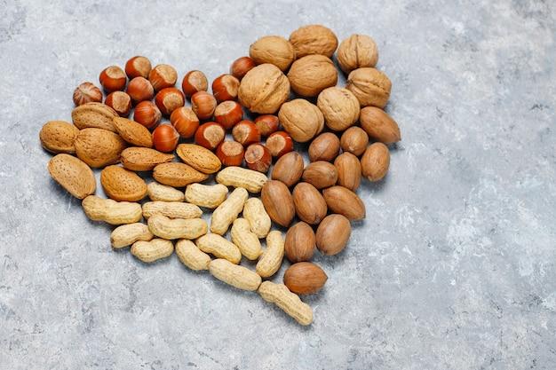 Assortiment van noten op betonnen ondergrond. hazelnoten, walnoten, pecannoten, pinda, amandelen, bovenaanzicht