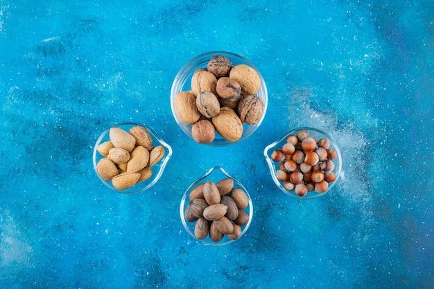 Assortiment van noten op een kommen, op de blauwe tafel.