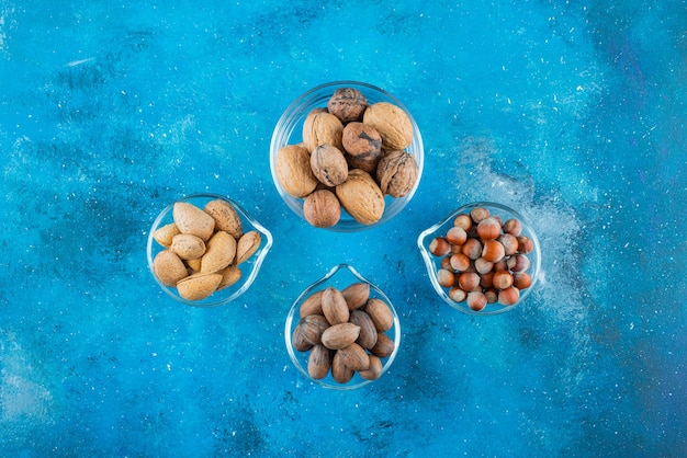 Assortiment van noten op kommen op het blauwe oppervlak