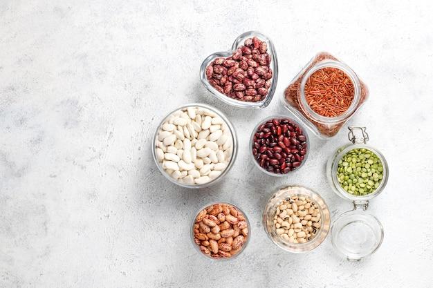 Assortiment van peulvruchten en bonen in verschillende kommen op lichte stenen achtergrond. bovenaanzicht. gezond vegan eiwitrijk voedsel.