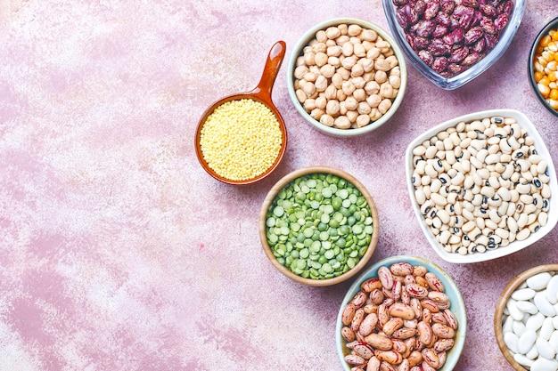 Assortiment van peulvruchten en bonen in verschillende kommen op lichte stenen tafel. bovenaanzicht. gezond veganistisch eiwitrijk voedsel.