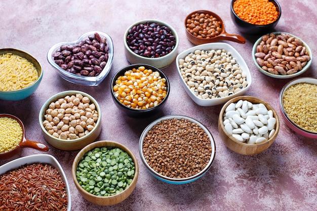 Assortiment van peulvruchten en bonen in verschillende kommen op lichtstenen tafel. bovenaanzicht. gezond vegan eiwitrijk voedsel.
