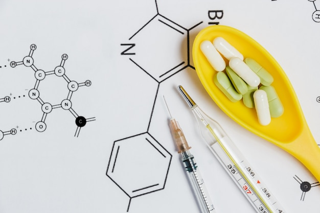 Assortiment van pillen en capsules in gele lepel, spuit, thermometer met chemische formule.