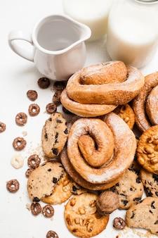 Assortiment van producten die met melk eten. gebak biologisch ontbijt, close-up bovenaanzicht. volkoren scones en gebakken broodjes met flessen en kruik lactodrank