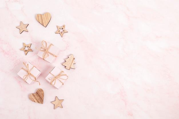 Assortiment van scandinavische stijl, eco-vriendelijke, handgemaakte kerstversieringen en cadeautjes op roze marmeren achtergrond, plat leggen, bovenaanzicht met kopie ruimte