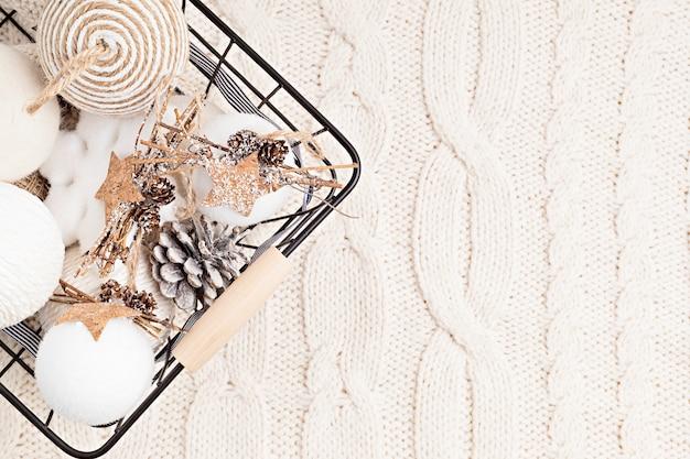 Assortiment van scandinavische stijl, gezellige eco-vriendelijke, handgemaakte kerstornamenten op licht gebreide achtergrond in de mand, plat leggen, bovenaanzicht met kopie ruimte