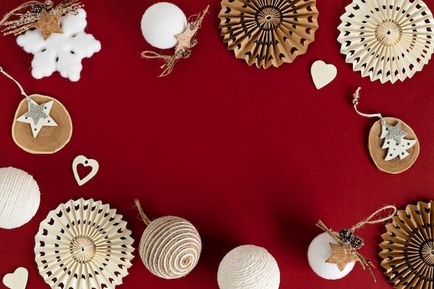 Assortiment van scandinavische stijl, gezellige eco-vriendelijke, handgemaakte kerstornamenten op rode achtergrond, plat leggen, bovenaanzicht met kopie ruimte